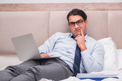 The businessman working in the bed at home Royalty Free Stock Photo
