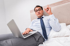 The businessman working in the bed at home Royalty Free Stock Photography