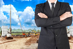 Businessman working in building construction site against blue s Royalty Free Stock Photos