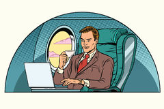 Businessman working in the business class cabin Stock Images