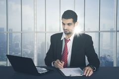 Businessman working on a business report with laptop. In a modern office Royalty Free Stock Images