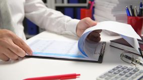 Businessman working and calculating, reads and writes reports. Office employee, table closeup. Business financial accounting conce. Pt.n stock footage