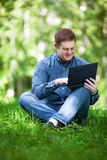 Businessman working in the city park. Successful smiling businessman working with laptop in the city park Stock Image