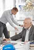 Businessman working with colleague in background Stock Images