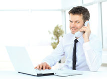 Businessman working at the compute. R talking on the phone and smiling Stock Photography