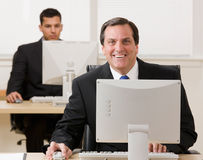 Businessman working on computer. Happy businessman working on computer with co-worker in background Royalty Free Stock Photo