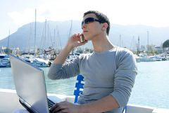 Businessman working with computer on a boat Stock Images
