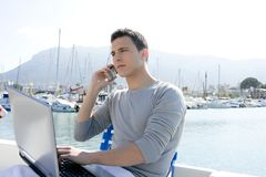 Businessman working with computer on a boat. Nice outdoor office Stock Image
