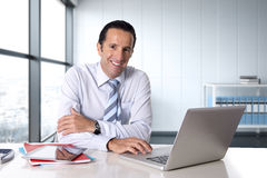 Businessman working on computer laptop sitting at desk looking confident Stock Images