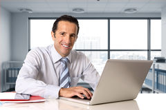 Businessman working on computer laptop sitting at desk looking confident Royalty Free Stock Image