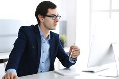 Businessman working with computer in modern office. Headshot of male entrepreneur or company manager at workplace. Business concept royalty free stock photo