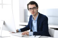 Businessman working with computer in modern office. Headshot of male entrepreneur or company manager at workplace. Business concept stock photos
