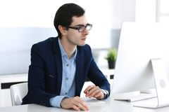 Businessman working with computer in modern office. Headshot of male entrepreneur or company manager at workplace. Business concept stock photo