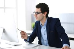 Businessman working with computer in modern office. Headshot of male entrepreneur or company manager at workplace. Business concept stock images