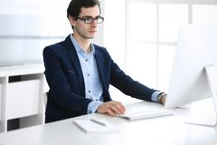 Businessman working with computer in modern office. Headshot of male entrepreneur or company manager at workplace. Business concept royalty free stock photography