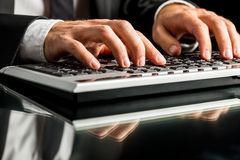 Businessman working on computer by typewriting. Hands of a businessman working on computer by typewriting on the keyboard, on a glass desk with reflection Royalty Free Stock Photos