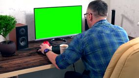 Businessman working at a computer typing data. Businessman working at a desktop computer typing data in an over the shoulder view of a large blank green screen stock video footage