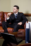 Businessman working on couch thinking in office Stock Photos