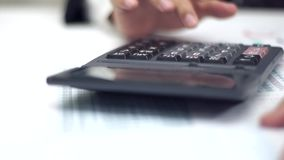 Businessman working with data sheet and using calculator. Closed up stock footage