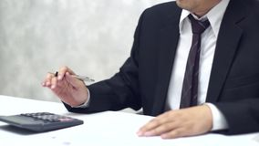 Businessman working with data sheet and using calculator. Got angry stock video footage