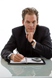 Businessman working at desk. Smiling businessman working at desk, white background Royalty Free Stock Images