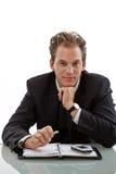 Businessman working at desk. Smiling businessman working at desk, white background Stock Images