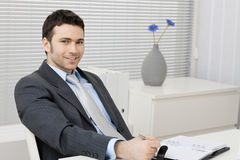 Businessman working at desk. Happy young businessman working at desk at office, smiling Stock Photography