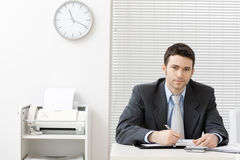 Businessman working at desk. Happy young businessman working at desk at office, smiling Royalty Free Stock Photo