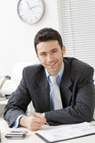 Businessman working at desk. Happy young businessman working at desk at office, smiling Stock Photo