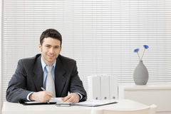 Businessman working at desk. Happy young businessman working at desk at office, smiling Royalty Free Stock Image