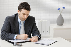 Businessman working at desk. Young businessman working at desk at office Stock Photography