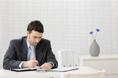 Businessman working at desk. Young businessman working at desk at office Royalty Free Stock Photos