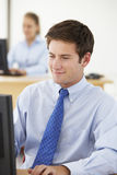 Businessman Working At Desk In Busy Office Royalty Free Stock Photography