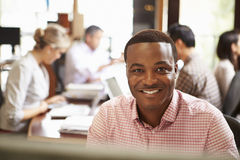 Businessman Working At Desk With Meeting In Background. Businessman Working At Desk In Architect Office With Meeting In Background Smiling At Camera Stock Photography