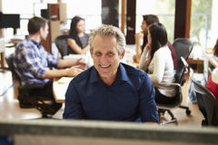 Businessman Working At Desk With Meeting In Background. Happy Businessman Working At Desk Smiling With Meeting In Background Royalty Free Stock Image