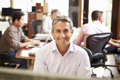 Businessman Working At Desk With Meeting In Background. Businessman Working At Desk Smiling At Camera With Meeting In Background Stock Photo
