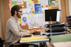 Businessman working at desk in office. Side view of businessman working at desk in office Stock Photography