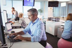 Businessman working at desk while sitting on exercise ball. In office Stock Photography