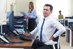 Businessman Working At Desk Suffering From Backache. Businessman Working At Desk Suffers From Backache Royalty Free Stock Photos
