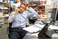 Businessman Working At Desk In Warehouse Stock Images