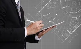 Businessman working on digital tablet with Architectural blueprint plan drawing background, architect, real estate business concep Royalty Free Stock Images