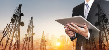 Businessman working digital tablet, with double exposure panoramic cityscape and telecommunication towers in sunrise Royalty Free Stock Images