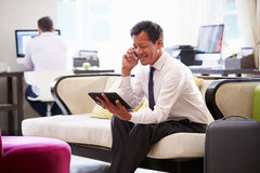 Businessman Working On Digital Tablet In Hotel Lobby Royalty Free Stock Photography