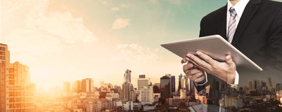 Businessman working on digital tablet outdoor, and city panoramic background Royalty Free Stock Photo