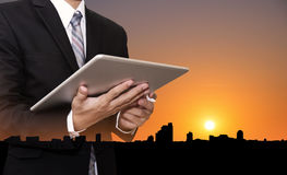 Businessman working on digital tablet, with silhouette buildings in the city in sunset background Royalty Free Stock Photo