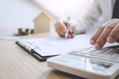 Businessman working doing finances and calculation cost of real estate investment while be signing to contract, Concept mortgage stock photos
