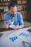 Businessman working with financial documents. Overhead view of businessman working with financial documents and drinking coffeee at home office Stock Photo