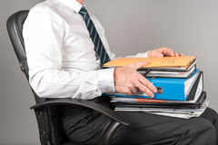 Businessman working with folders on his knees Stock Images
