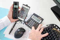 Businessman working on four different equipements Royalty Free Stock Photography