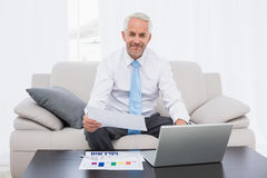 Businessman working on graphs and laptop at home Stock Photography